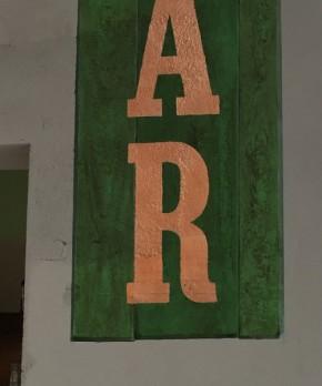 Muurschildering in Antibes Green als basiskleur, en houtnerven in Verniswas Gouden Den. De letters zijn van koper bladmetaal.